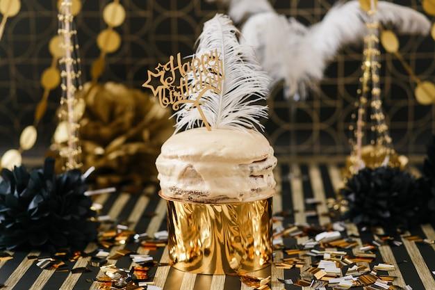 Bolo da festa de anos com os vários balões dourados e pretos da decoração. Foto gratuita