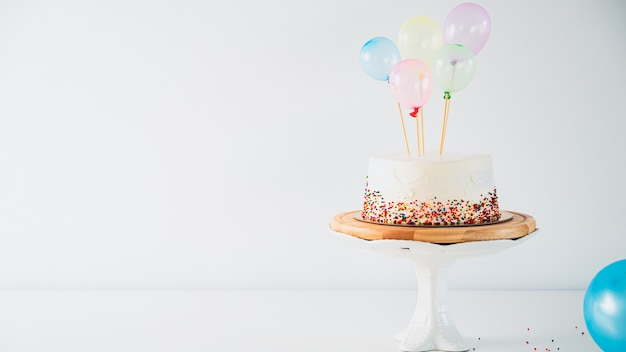 Bolo de aniversário branco e balões coloridos sobre cinza claro. aniversário do conceito de comida. Foto Premium