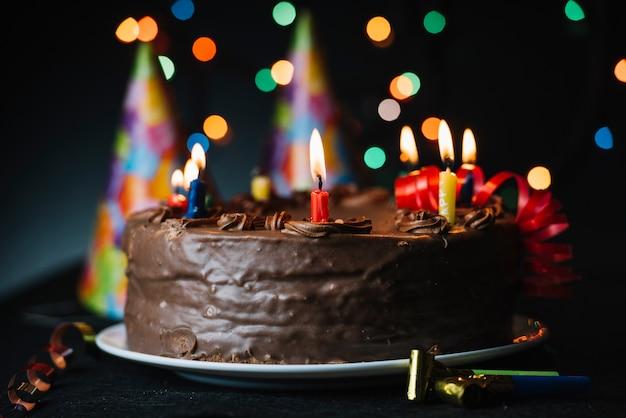 Bolo de aniversário com uma vela iluminada contra o pano de fundo de luz e chapéu de festa Foto gratuita