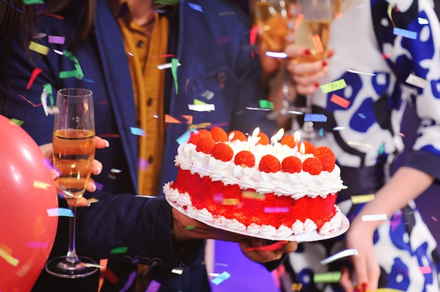 Bolo de aniversário com velas close-up no fundo da companhia alegre dos meus melhores amigos Foto Premium