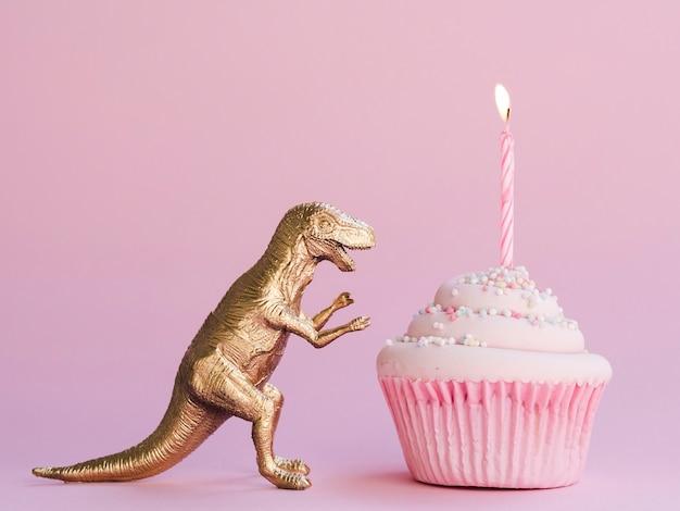 Bolo de aniversário e dinossauro engraçado em fundo rosa Foto gratuita