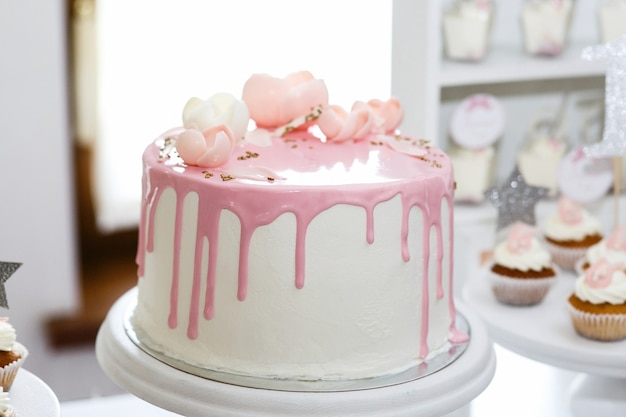 Bolo de aniversário impressionante coberto com glacé rosa e rosas Foto gratuita