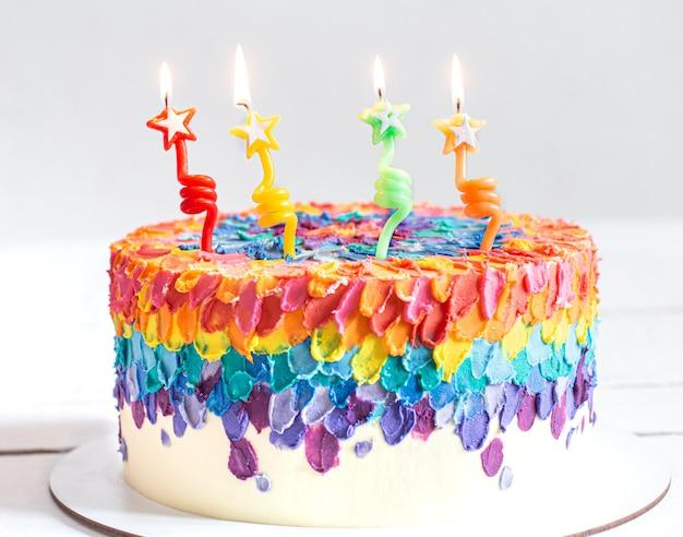 Bolo de aniversário multicolorido decorado com velas acesas em forma de estrelas. conceito de feliz quarto aniversário. Foto Premium