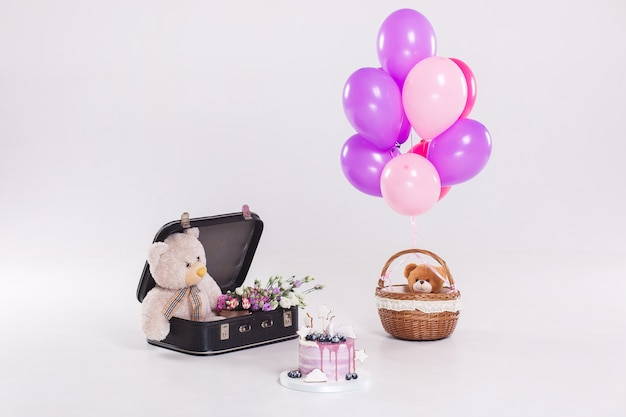 Bolo de aniversário, ursinho de pelúcia em suitecase vintage e balões isolados no fundo branco Foto gratuita