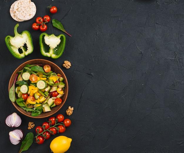 Bolo de arroz tufado; legumes; salada e noz no balcão da cozinha preto Foto gratuita
