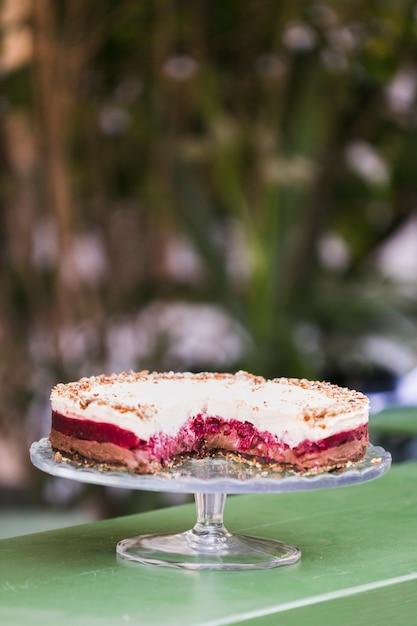 Bolo de camada saboroso no bolo ficar contra o fundo desfocado Foto gratuita