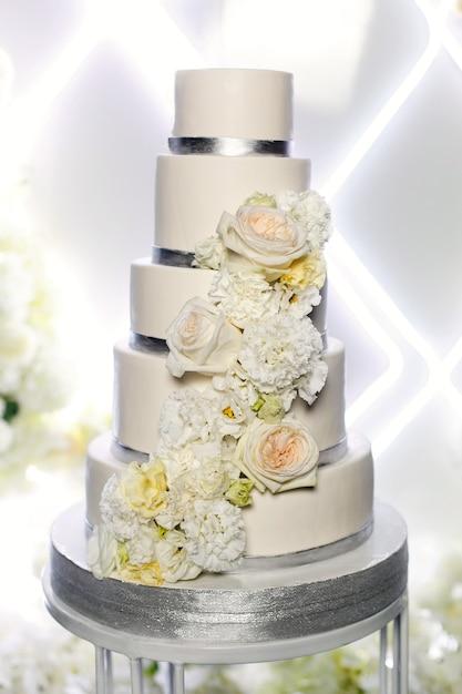 Bolo de casamento bonito festivo decorado com flores isoladas perto acima. bolo de casamento em camadas branco isolado. barra de chocolate na festa de casamento. dia do casamento. Foto Premium