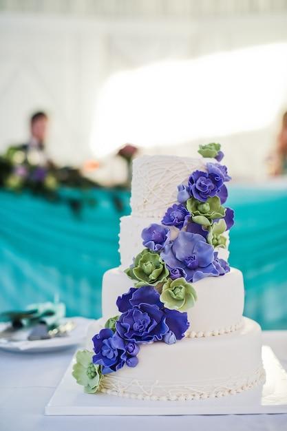 Bolo de casamento branco decorado com flores azuis Foto Premium