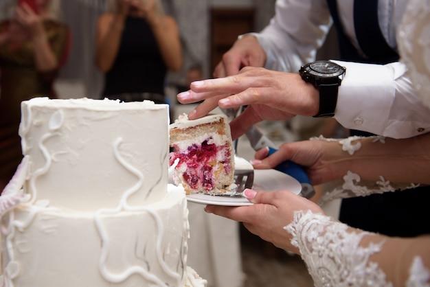 Bolo de casamento. uma noiva e um noivo estão cortando o bolo de casamento Foto Premium