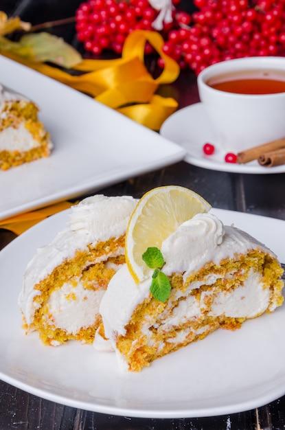Bolo de cenoura com cream cheese, fatias de laranja e limão e folhas de hortelã por cima Foto Premium