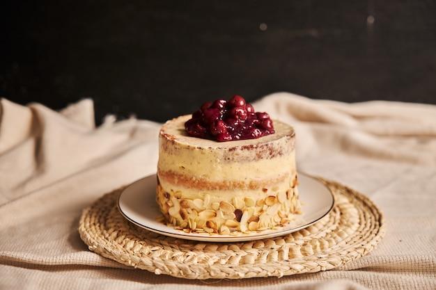 Bolo de cereja com creme em um prato branco com fundo desfocado Foto gratuita