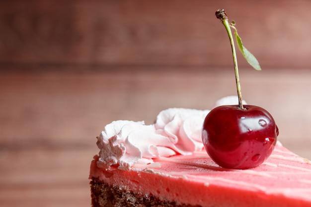 Bolo de chocolate com cerejas no fundo de madeira. Foto Premium