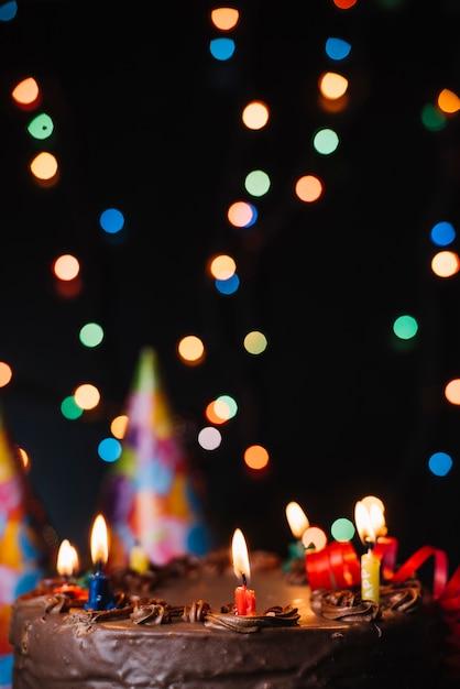 Bolo de chocolate com velas iluminadas decorado com luzes de borrão Foto gratuita