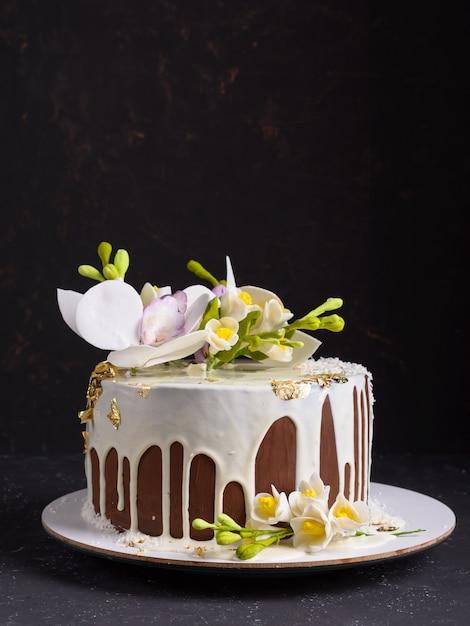 Bolo de chocolate decorado com flores e derramou o glacê branco. copyspace Foto Premium