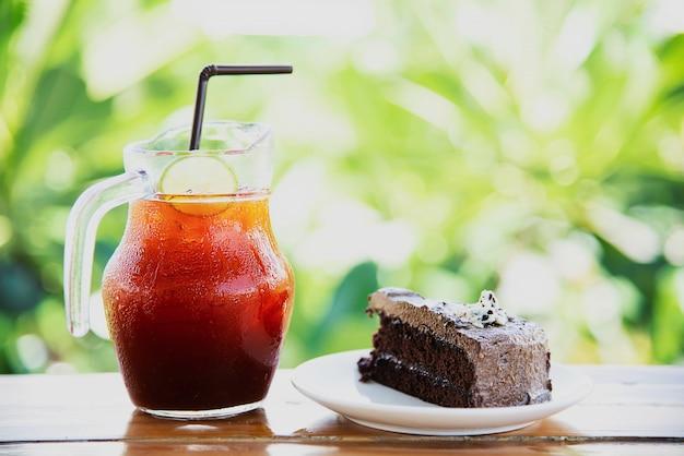 Bolo de chocolate na mesa com chá gelado sobre jardim verde - relaxar com bebidas e padaria no conceito de natureza Foto gratuita
