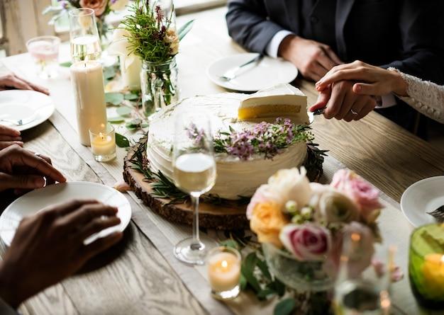 Bolo de corte de noiva e noivo na recepção de casamento Foto Premium