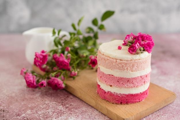 Bolo de creme e bagas-de-rosa lindo Foto Premium