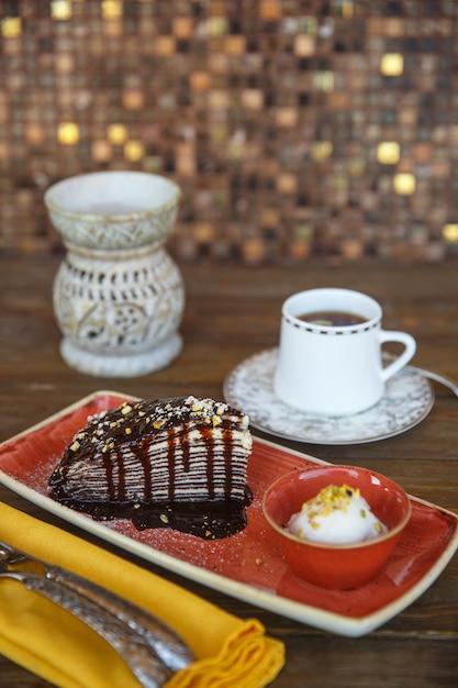 Bolo de crepe de chocolate com sorvete de baunilha, servido com chá Foto gratuita