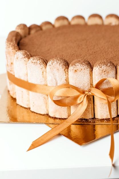 Bolo de esponja clássico tiramisu com cacau, bolos caseiros. bolo de tiramisu close-up. Foto Premium