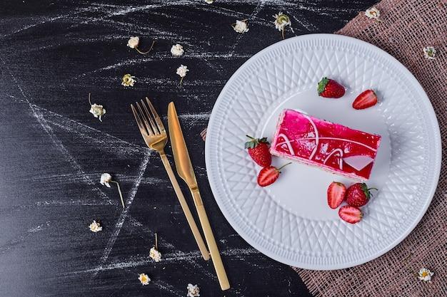Bolo de frutas com morangos em um prato branco com talheres de ouro. Foto gratuita