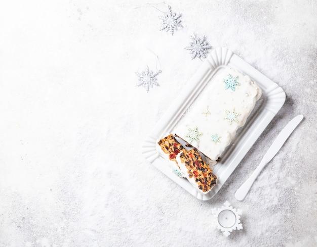 Bolo de frutas de natal, pudim em fundo nevado. doces de ano novo Foto Premium