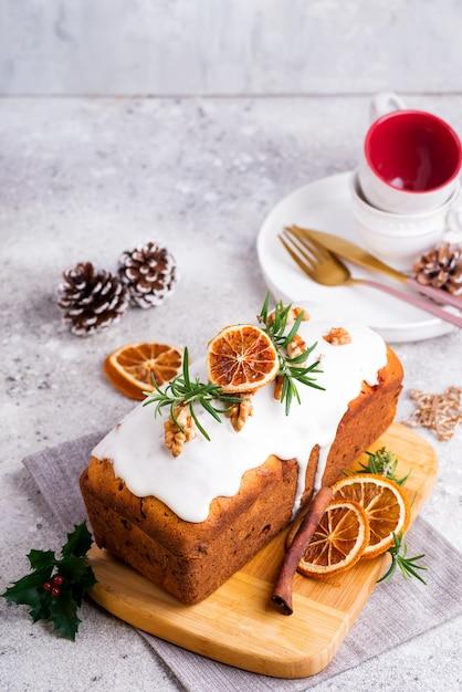 Bolo de frutas polvilhado com glacê, nozes e laranja seca na pedra. bolo caseiro de férias de natal e inverno Foto Premium