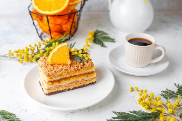 Bolo de laranja decorado com fatias de laranja frescas e flores de mimosa na luz Foto gratuita