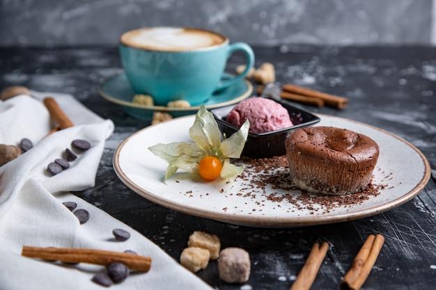 Bolo de lava de chocolate derretido com sorvete no prato e cappuccino. bolas de sorvete no copo. espaço preto escuro. Foto Premium