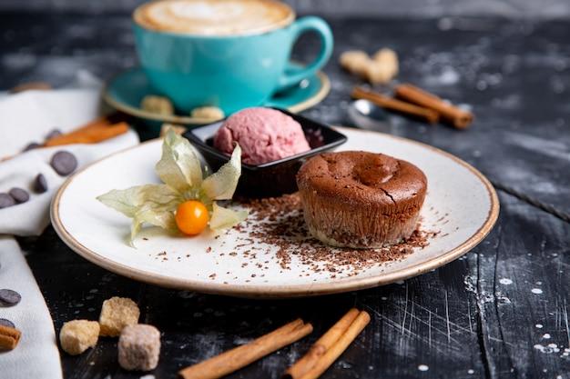 Bolo de lava de chocolate derretido com sorvete no prato e cappuccino. bolas de sorvete no copo. parede preta escura. Foto Premium