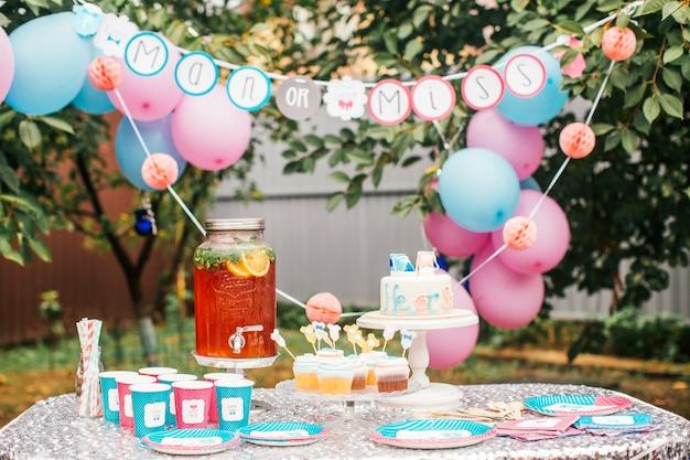 Bolo de menino ou menina e guloseimas diferentes para festa de chá de bebê na mesa ao ar livre Foto Premium