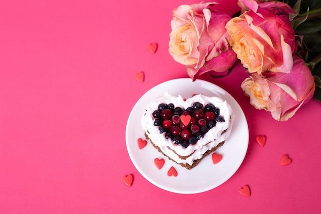 Bolo de mini sobremesa romântica para dia dos namorados com rosas. biscoitos doces com cobertura de creme e coração vermelho para decoração em rosa. close-up, copie o espaço. Foto Premium