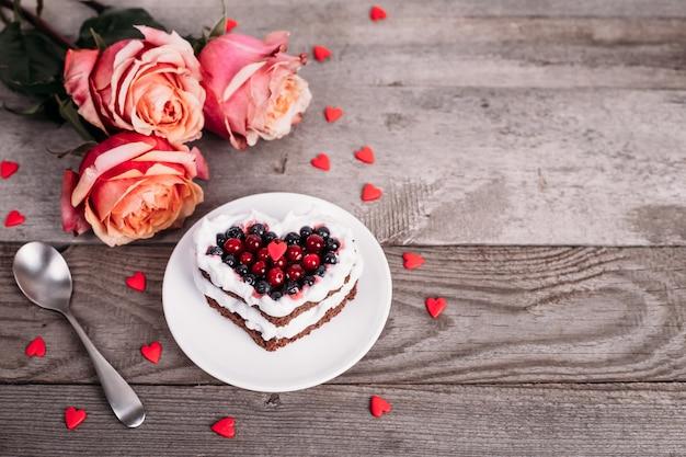 Bolo de mini sobremesa romântica para dia dos namorados com rosas. biscoitos doces com cobertura de creme e coração vermelho para decoração na mesa de madeira. close-up, copie o espaço. Foto Premium