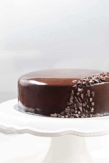 Bolo de mousse de chocolate com esmalte espelho em um carrinho de bolo Foto Premium