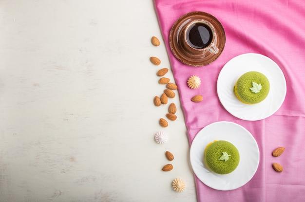 Bolo de mousse verde com creme de pistache e uma xícara de café. vista superior, copyspace. Foto Premium