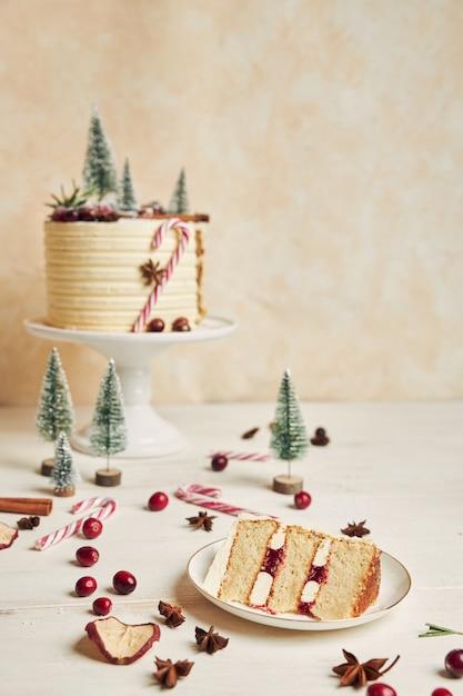 Bolo de natal com enfeites e um pedaço de bolo no prato Foto gratuita
