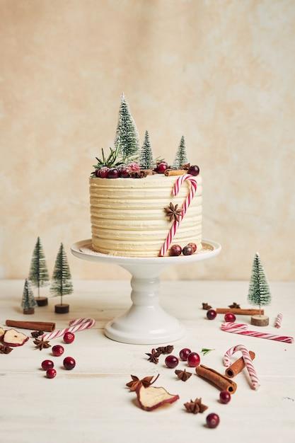 Bolo de natal decorado com árvores, frutas vermelhas e paus de canela Foto gratuita