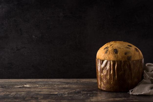 Bolo de panetone de chocolate de natal com natal decorado na mesa de madeira copie o espaço Foto Premium