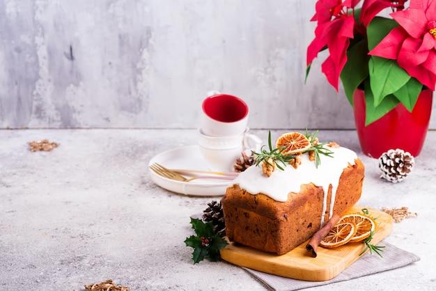 Bolo de pão de frutas polvilhado com glacê, nozes e laranja seca na pedra. bolo caseiro de férias de natal e inverno Foto Premium