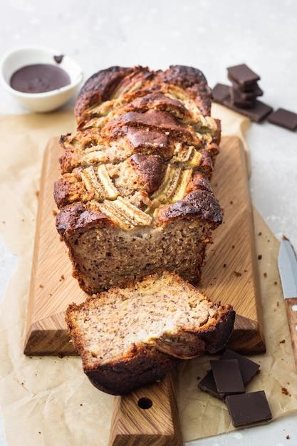 Bolo de pão ou pão de banana com chocolate numa tábua de madeira Foto Premium