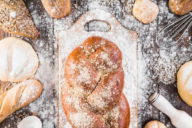 Bolo de pão trançado em cortar a placa com farinha por cima da mesa Foto gratuita