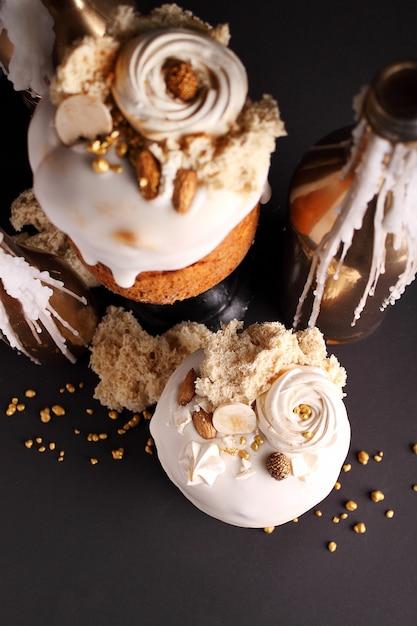 Bolo de páscoa com passas e frutas cristalizadas em esmalte branco é decorado com nozes, biscoito molecular e merengue Foto Premium