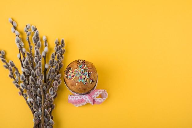 Bolo de páscoa com ramos de salgueiro na mesa Foto gratuita