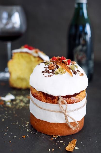 Bolo de páscoa e copo de vinho tinto. composição de páscoa com pão doce ortodoxo, kulich e garrafa de vinho em fundo escuro Foto Premium
