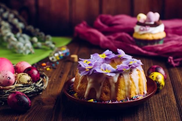 Bolo de páscoa tradicional decorado com flores de prímula e ovos pintados em ninho natural Foto Premium