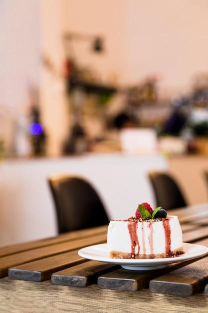 Bolo de queijo com frutas e hortelã na mesa de madeira no café Foto gratuita