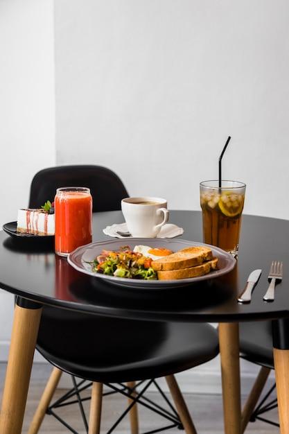 Bolo de queijo; smoothie; café; suco e café da manhã na mesa redonda preta Foto gratuita
