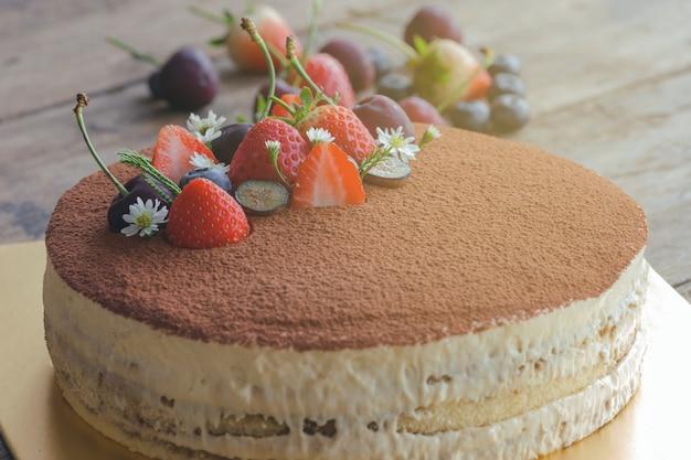 Bolo de tiramisu redondo na mesa de madeira polvilhe com cacau em pó e decorado com frutas frescas Foto Premium