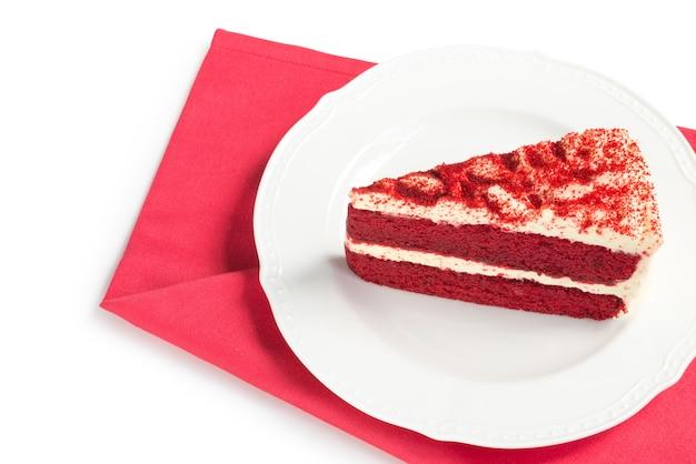 Bolo de veludo vermelho cortado em pedaços na chapa branca sobre vermelho placemat Foto Premium