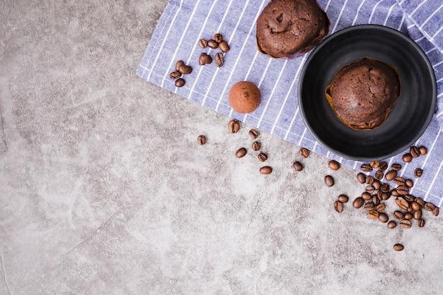 Bolo do copo e grãos de café torrados no guardanapo sobre o fundo de concreto Foto gratuita