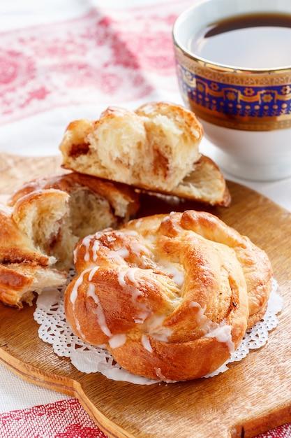 Bolo doce caseiro fresco do redemoinho da canela com esmalte e café preto para o café da manhã. Foto Premium